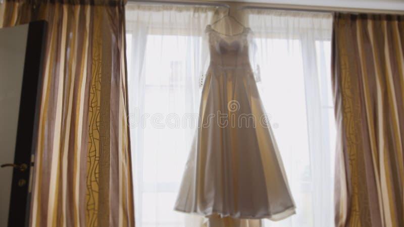 在窗口的美丽的婚礼礼服在新娘` s室 图库摄影