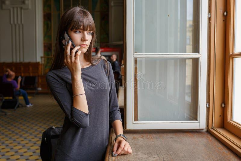 在窗口的美好的年轻女人身分与电话 免版税库存图片