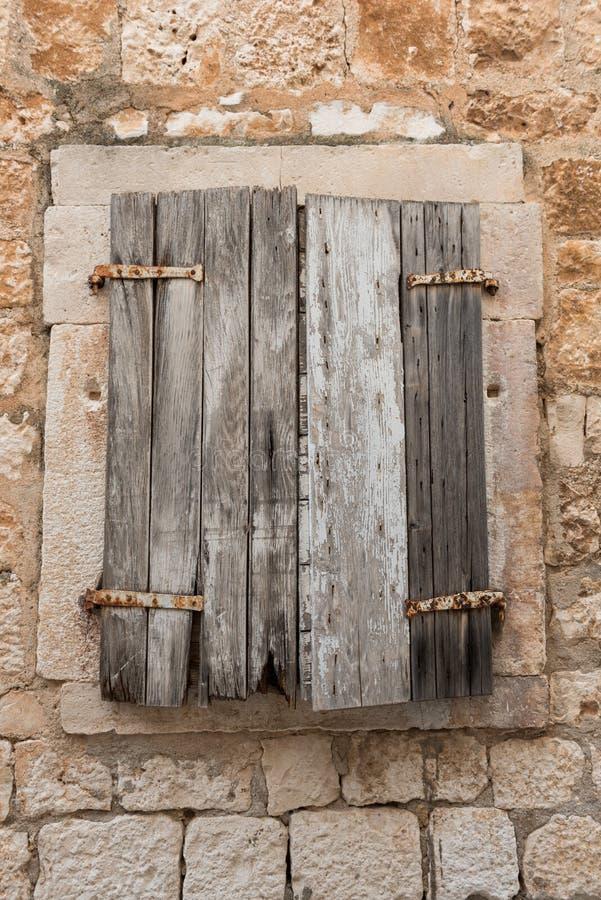 在窗口的老减速火箭的木快门 房子老石头 外部细节 木视窗 免版税图库摄影