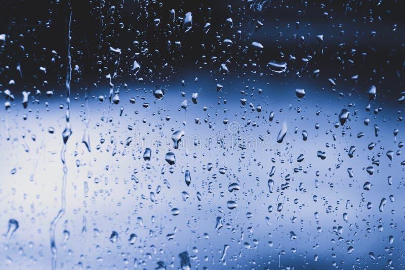 在窗口的蓝色雨珠 免版税库存照片