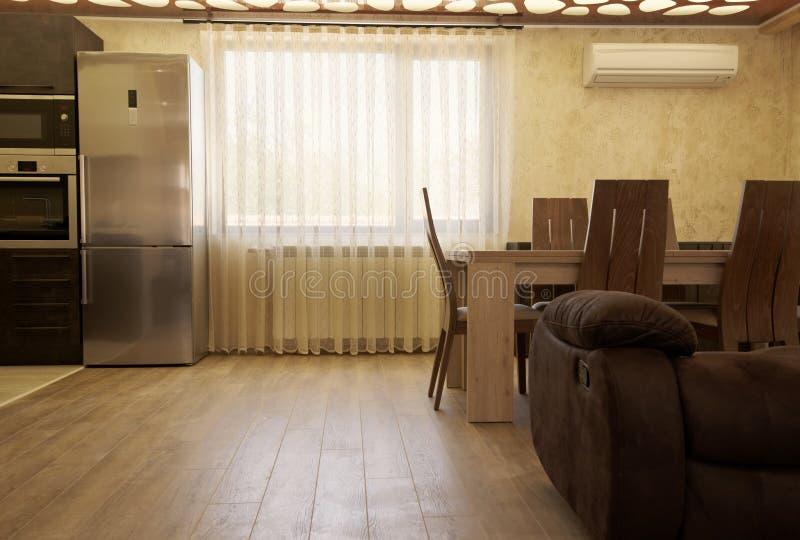在窗口的豪华帷幕 有厨房和餐桌片断的现代客厅  免版税库存照片