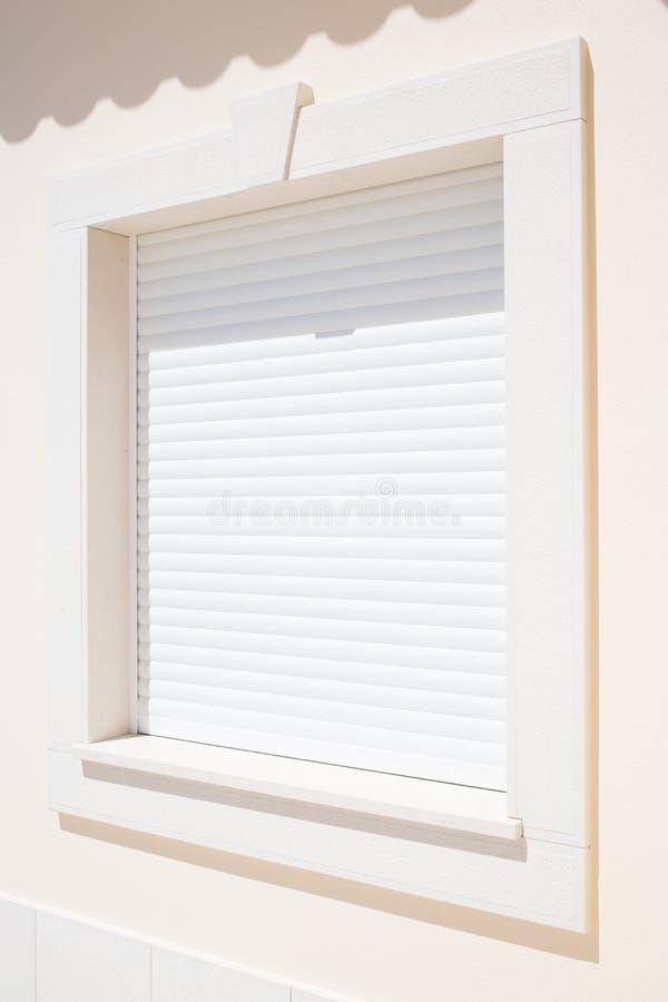 在窗口的闭合的白色塑料现代快门 库存图片