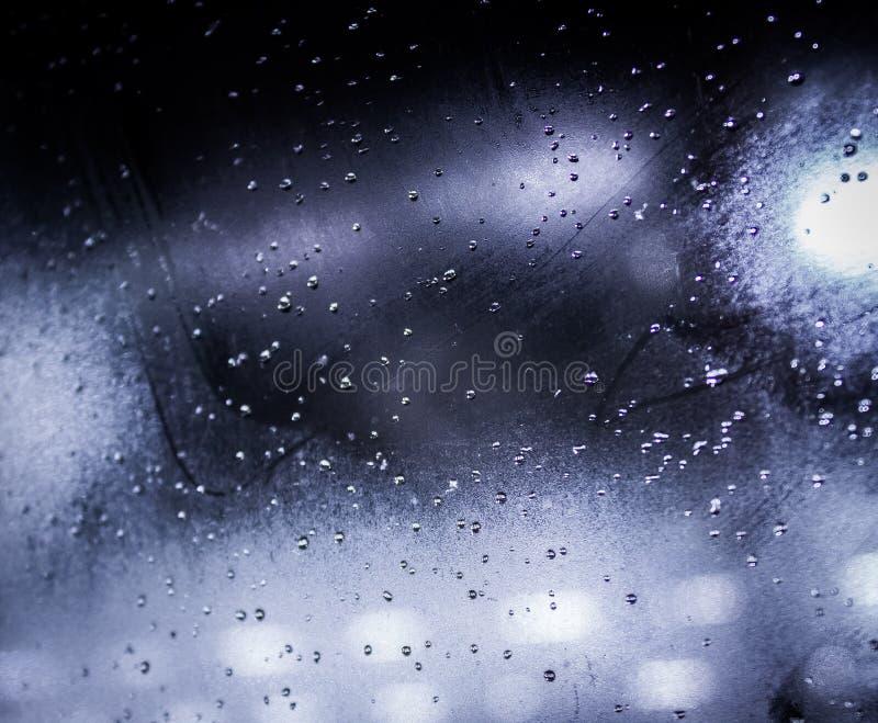 在窗口的雨下落与bokeh光 免版税库存图片