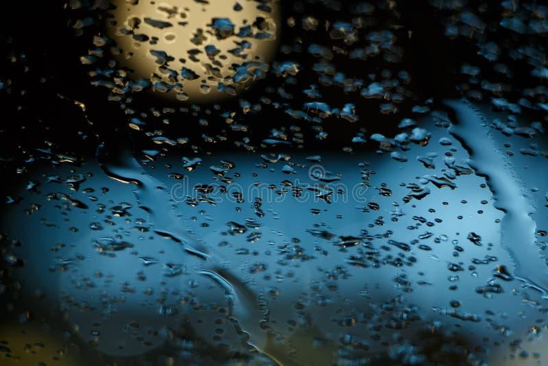 在窗口的雨下落和bokeh弄脏背景摘要 库存图片