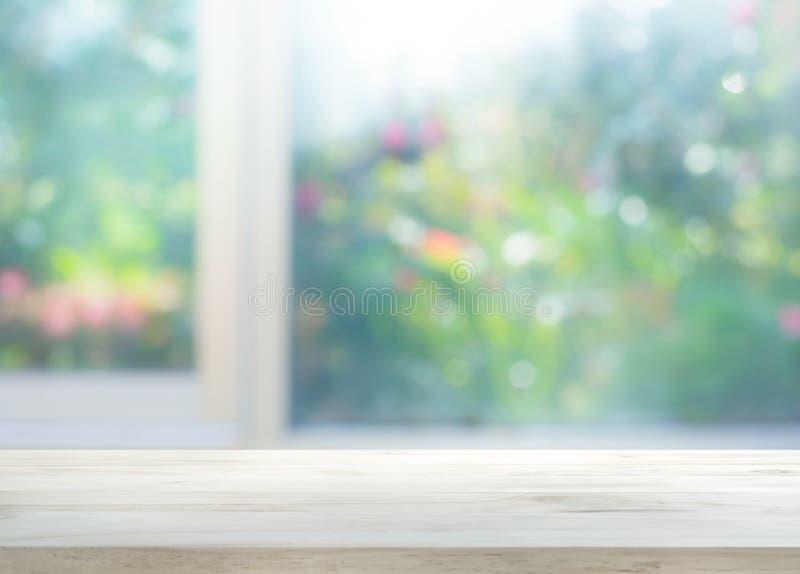 在窗口迷离的木台式有庭院花背景 库存照片
