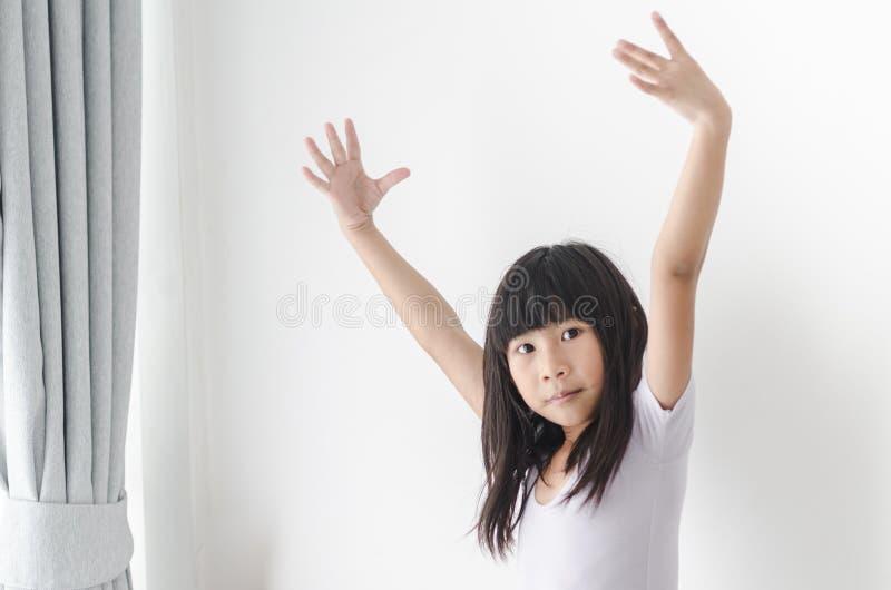 在窗口附近的女孩实践的芭蕾舞蹈 免版税库存照片