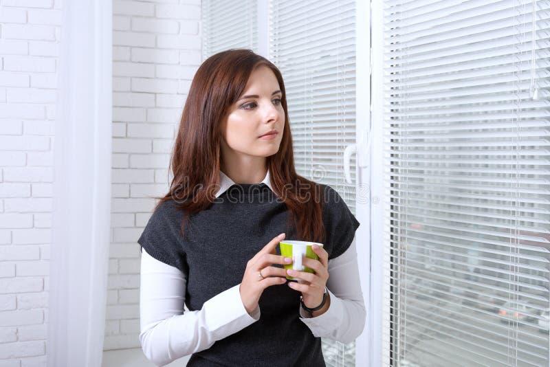在窗口附近的妇女饮用的咖啡 库存图片