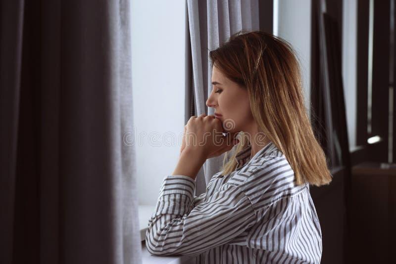 在窗口附近的孤独的沮丧的妇女 库存照片