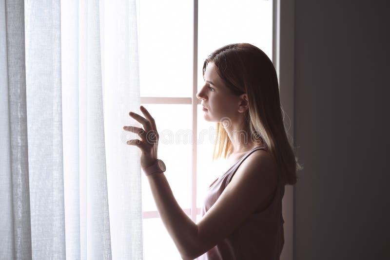在窗口附近的孤独的沮丧的妇女 图库摄影