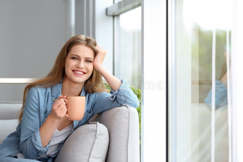 在窗口附近的少妇饮用的早晨咖啡在家 库存照片