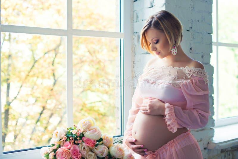 在窗口附近的怀孕的女孩 愉快的健康怀孕 免版税库存照片