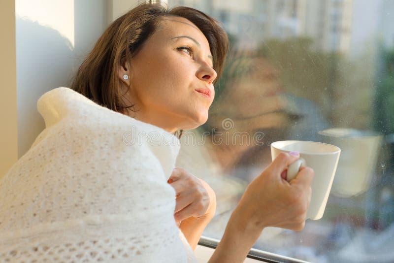 在窗口附近的成熟妇女身分与杯子在温暖的被编织的羊毛毯子下的热的饮料看梦想窗口, 免版税库存图片
