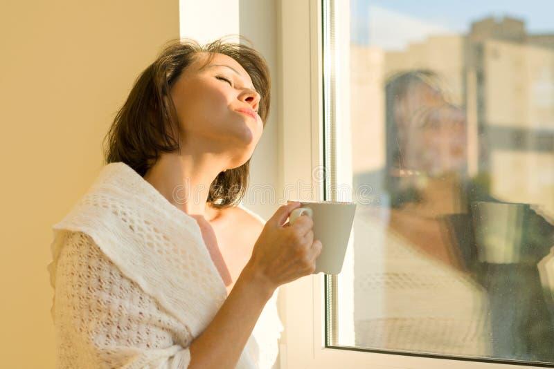 在窗口附近的成熟妇女身分与杯子在温暖的被编织的羊毛毯子下的热的饮料看梦想窗口, 免版税图库摄影