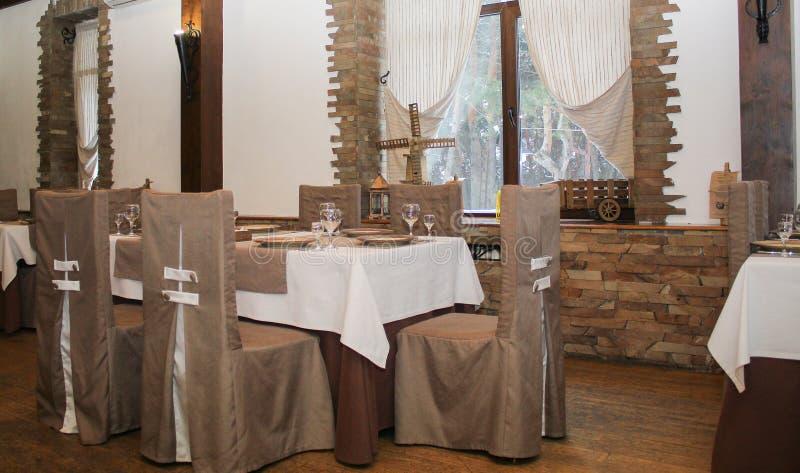 在窗口附近的服务的桌在咖啡馆 免版税库存照片