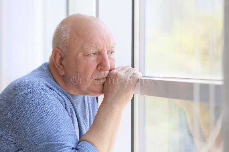 在窗口附近的沮丧的老人 免版税库存照片