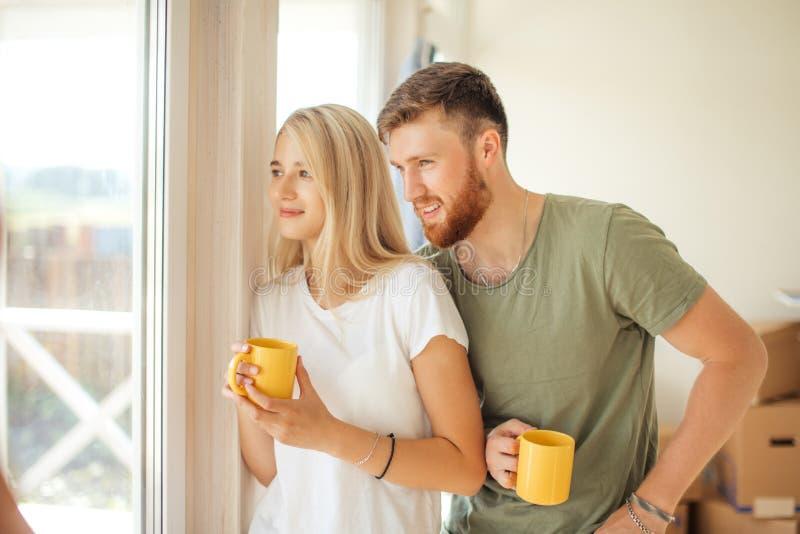 在窗口附近的男人和妇女饮用的茶 被买的新房或公寓 库存照片