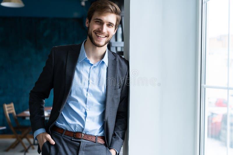 在窗口附近的确信的专业英俊的商人身分在他的办公室 免版税库存照片