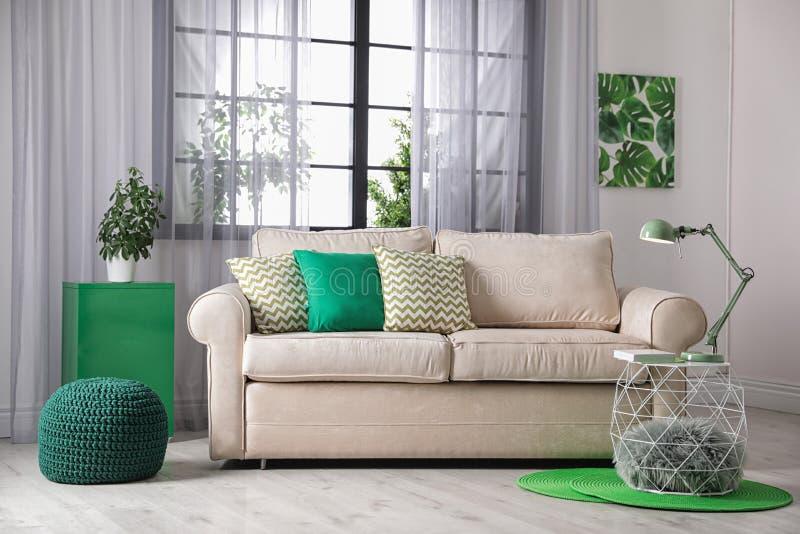在窗口附近的舒适的长沙发在现代屋子内部里 免版税库存照片