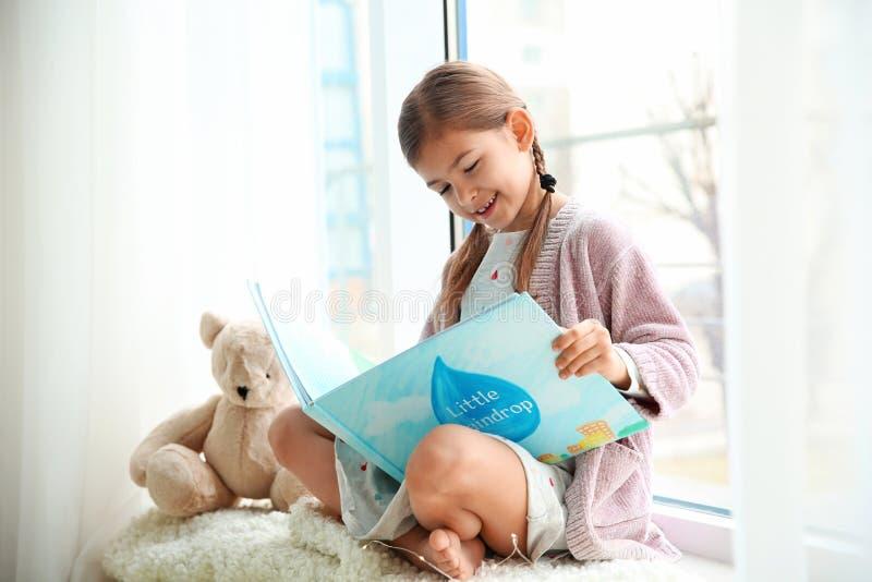 在窗口附近的逗人喜爱的女孩看书 图库摄影
