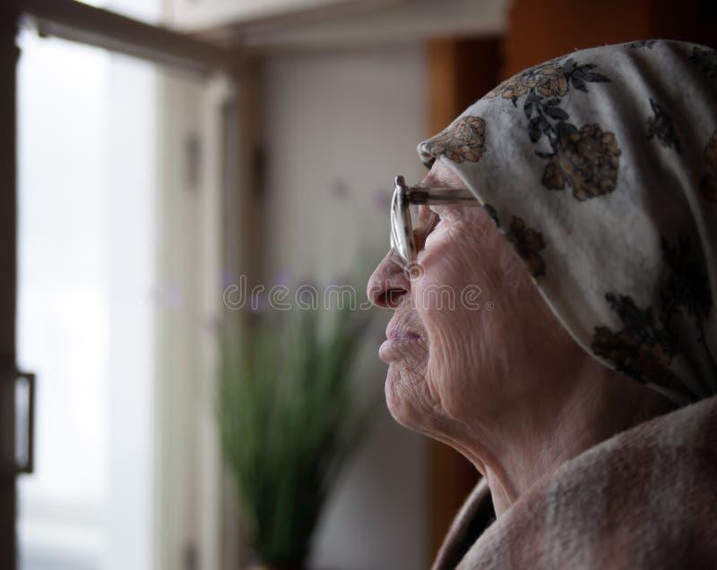 在窗口附近的年长妇女 图库摄影