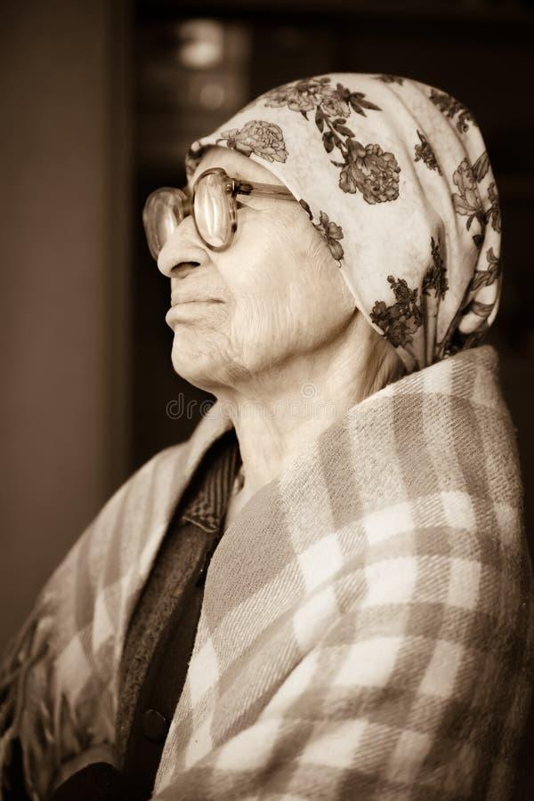 在窗口附近的年长妇女 免版税库存照片