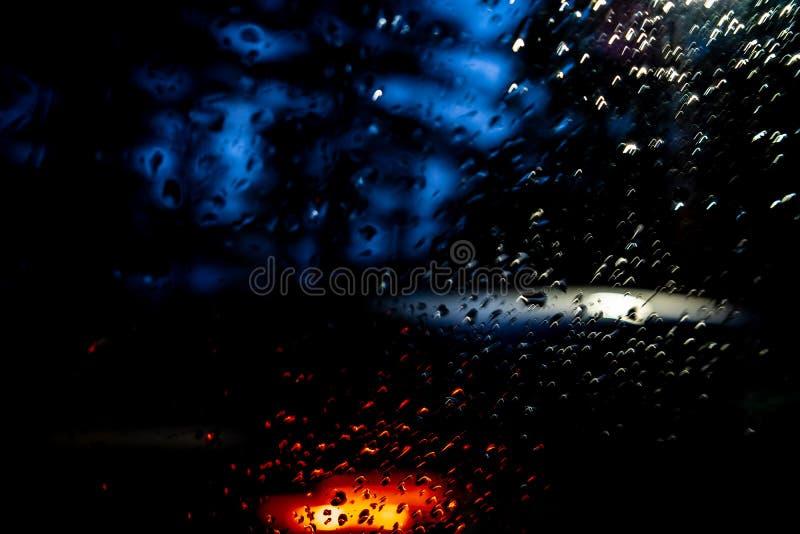 在窗口,从一辆移动的汽车的射击的雨下落 免版税库存照片
