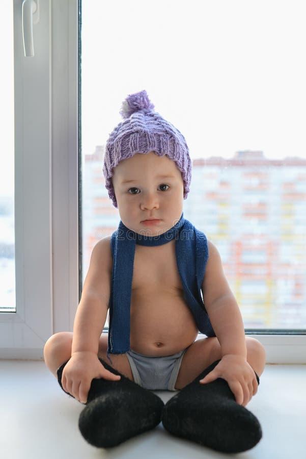 在窗台的可爱的一岁男婴偏僻的开会在冬天帽子、鞋子和围巾weared,户内 免版税图库摄影