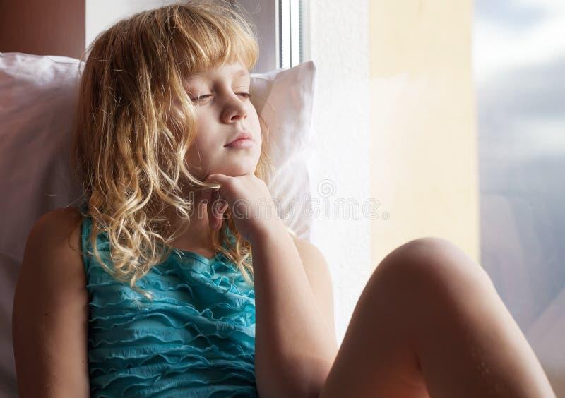 在窗台的小的白肤金发的困女孩位子 库存图片