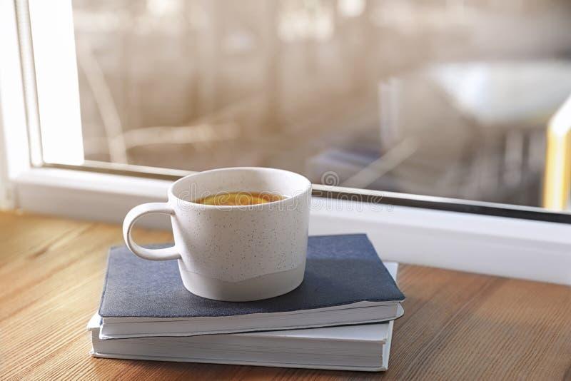 在窗台的杯冬天饮料和书 库存照片