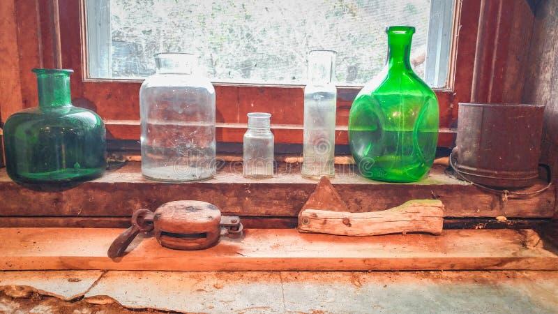 在窗台的绿色玻璃瓶子 免版税库存图片