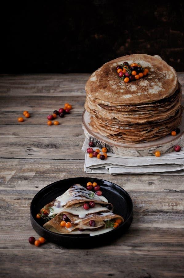 在立场的一张木桌上堆稀薄的薄煎饼用浓缩牛奶和莓果 免版税库存照片