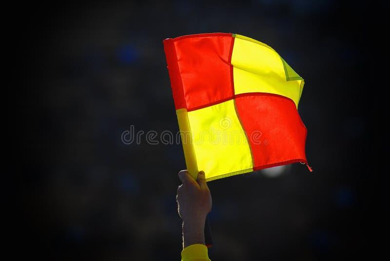 在立场的背景的橄榄球肮脏的旗子在足球比赛期间的 库存图片