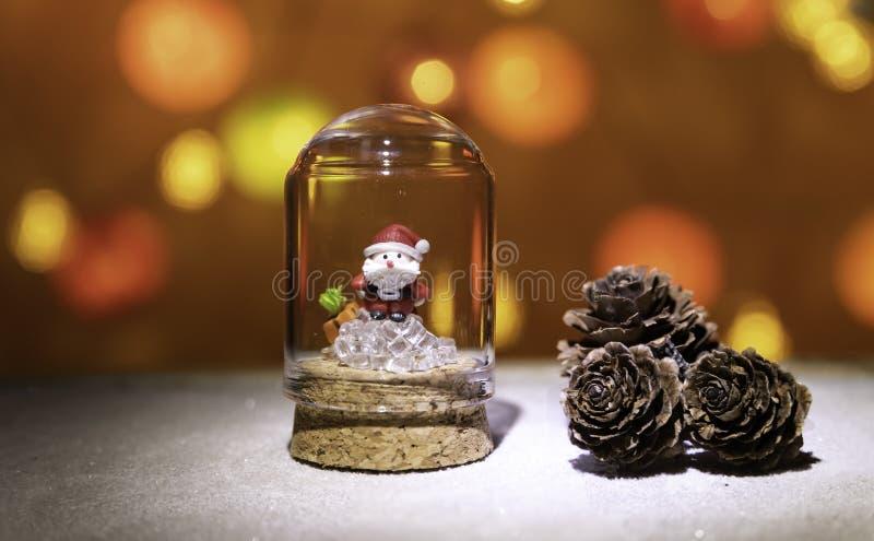 在立方体冰的圣诞老人项目在杉木锥体附近的玻璃管从圣诞灯背景 免版税库存图片