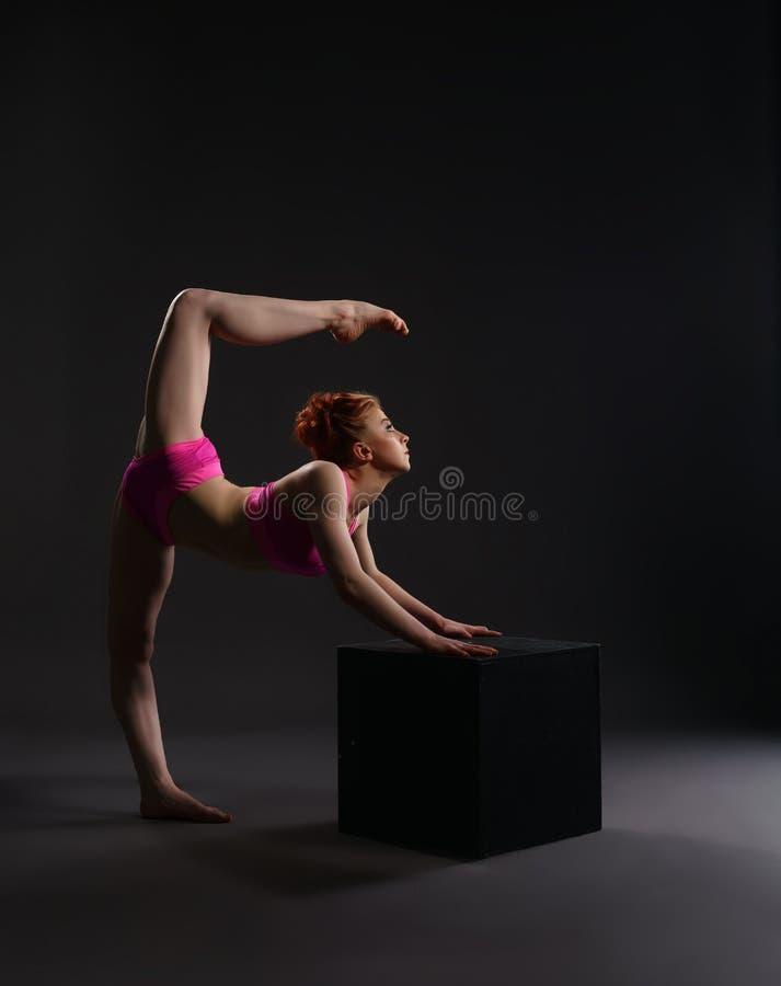 在立方体的灵活的舞蹈家训练在演播室 库存照片