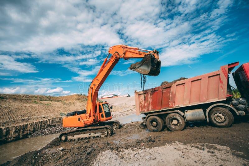 在站点,在大量掘土的工作期间的装载的倾销者卡车的运转的挖掘机 免版税库存图片