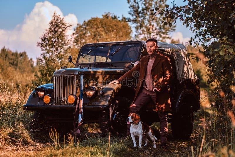 在站立与他的小猎犬狗一起的典雅的衣裳的猎人在一辆减速火箭的军用汽车附近在森林里 图库摄影