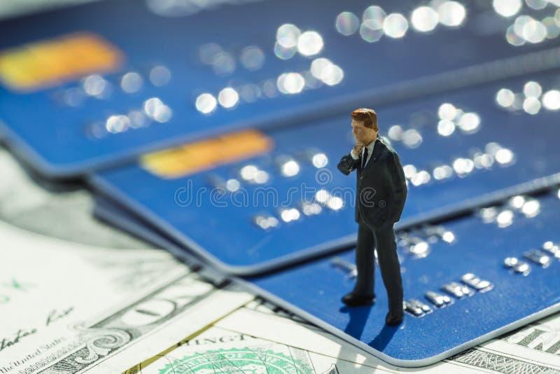 在站立和认为在美国dallar钞票和信用卡的衣服的微型商人使用作为网络购物,债务,金钱 库存图片