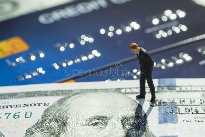 在站立和认为在美国dallar钞票和信用卡的衣服的微型商人使用作为网络购物,债务,金钱 图库摄影