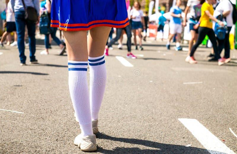 在站立在与体育场立场的一条连续轨道的白色运动鞋的女孩腿 免版税库存照片