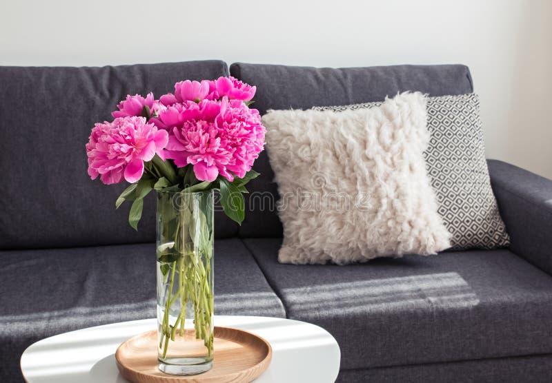 在站立在咖啡桌上的花瓶的牡丹在沙发附近 免版税库存照片