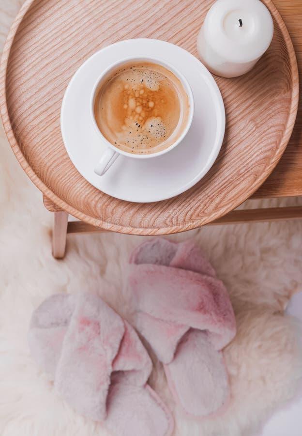 在站立在小桌和桃红色拖鞋上的木盘子的咖啡在地板上 库存照片