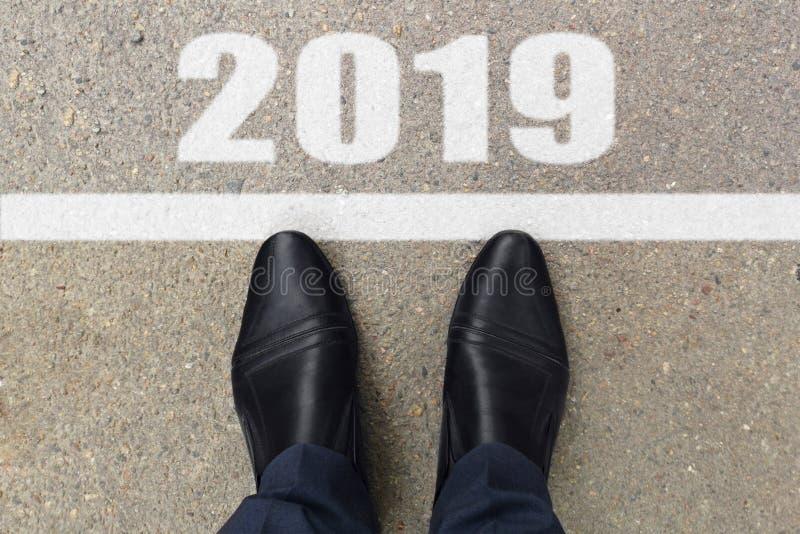 在站立在文本2019前的黑皮鞋的人脚绘在沥青,顶视图 免版税库存照片