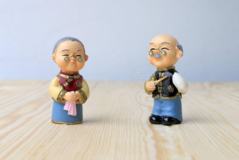 在站立在木背景的中国一致的样式的祖母和祖父玩偶 在春节 库存照片