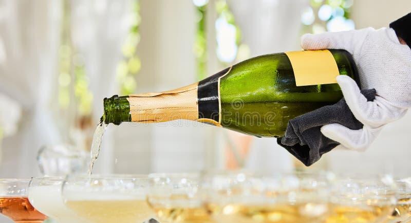 在站立在桌上的长笛的倾吐的香槟 库存照片