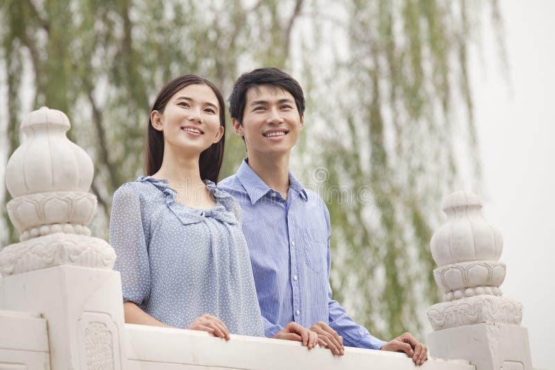 在站立在桥梁的爱的年轻夫妇 免版税库存图片