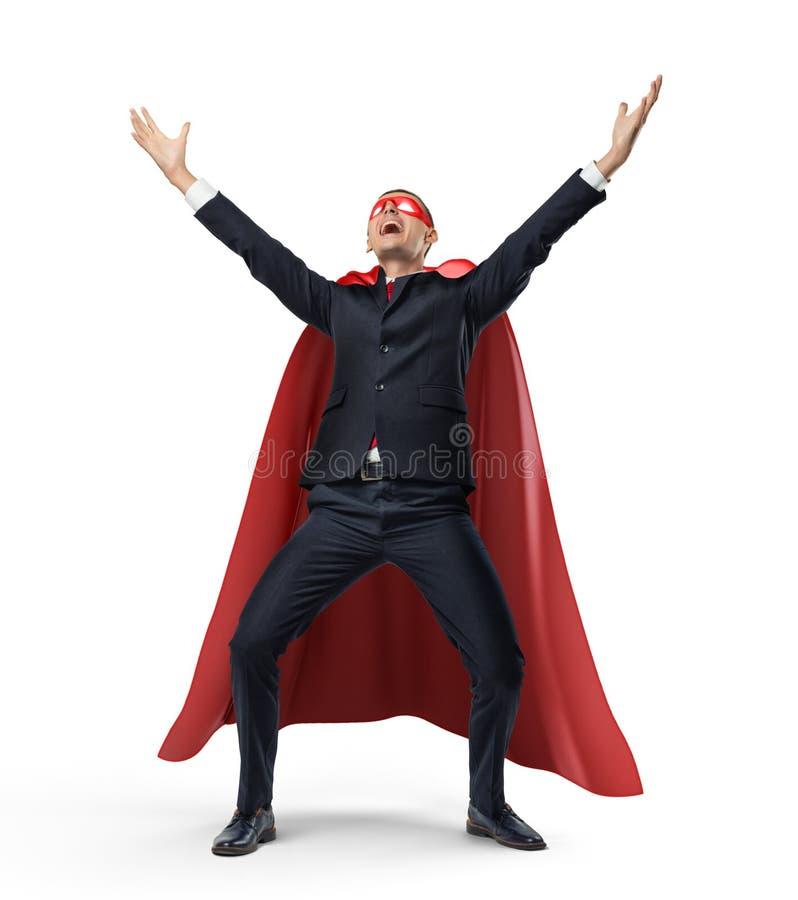 在站立在正面图的超级英雄红色海角和面具的一个商人用手在白色背景的胜利上升了 库存图片