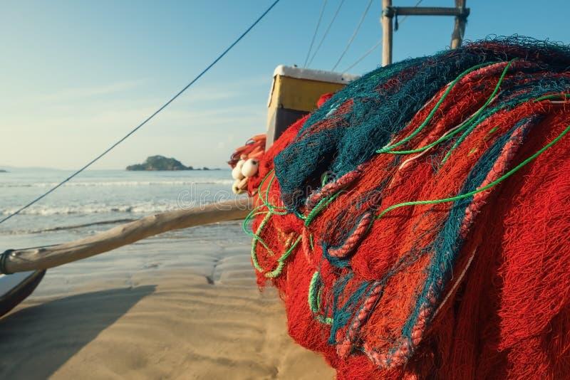 在站立在沙滩的小船的红色网在Weligama斯里兰卡 抓鱼传统方式  库存照片