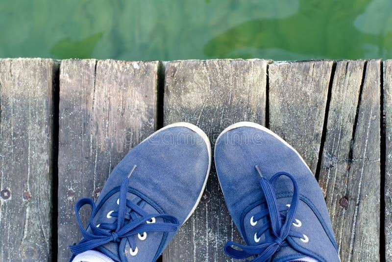 在站立在海的运动鞋的脚在夏天靠码头 库存照片