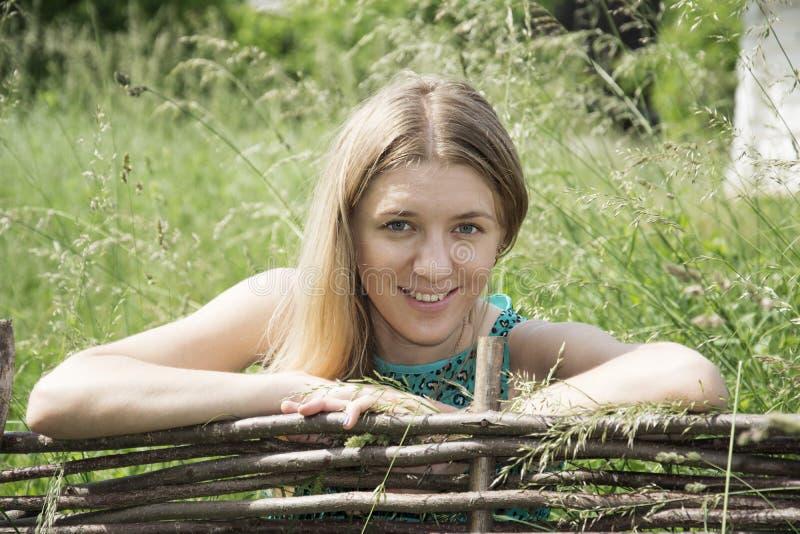 在站立在篱芭附近的夏天美丽的女孩 库存照片