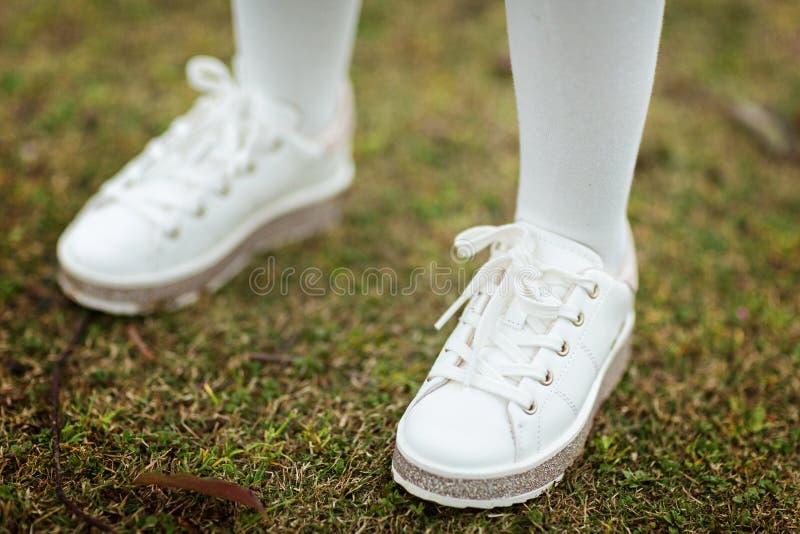 在站立在绿草的白色运动鞋的儿童的腿室外 免版税库存照片